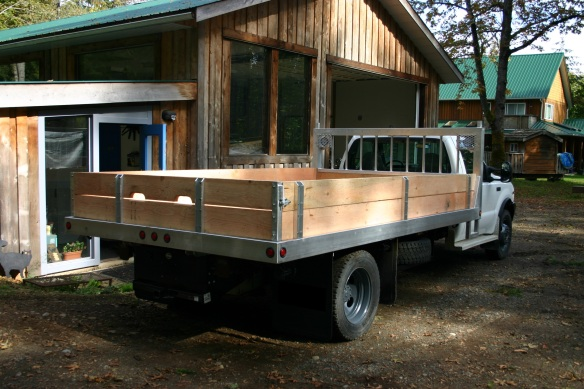 Aluminum and fir deck with stake sides and spare tire holder.